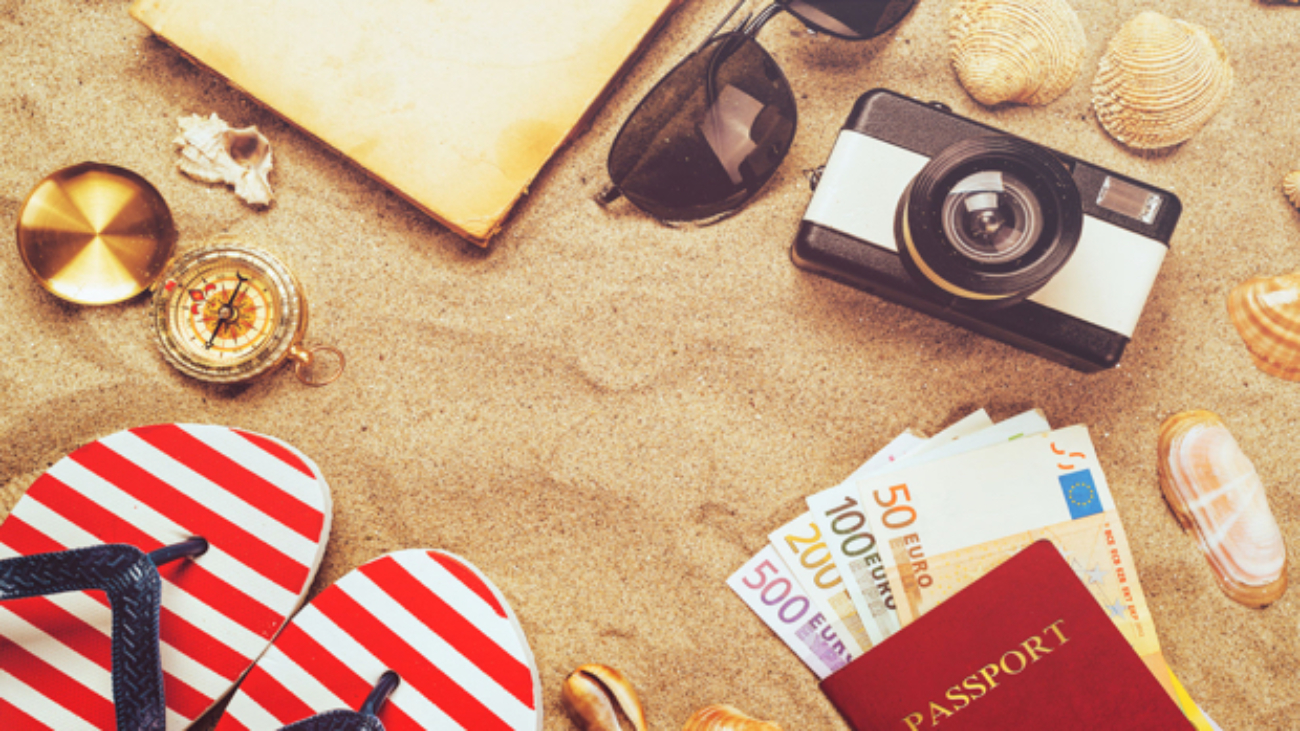 56956206 - summer vacation accessories on tropical sandy ocean beach, holidays abroad - summertime lifestyle objects and european euros in flat lay top view arrangement in warm sand.